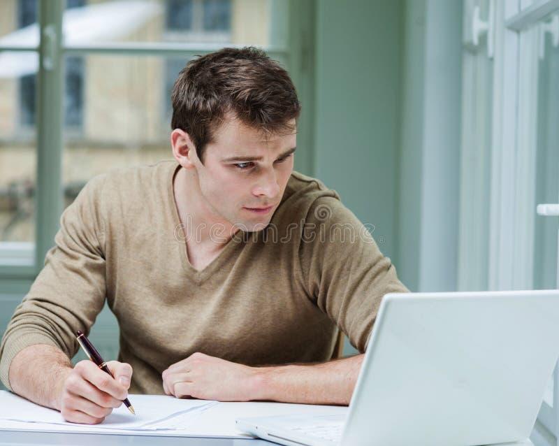 Hombre de negocios joven que mira el ordenador portátil mientras que escribe en documentos en oficina imagen de archivo