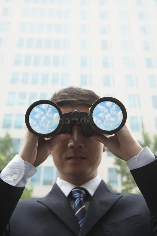Hombre de negocios joven que mira en la distancia a través de los prismáticos con las nubes y el cielo en las lentes de los prismá foto de archivo libre de regalías
