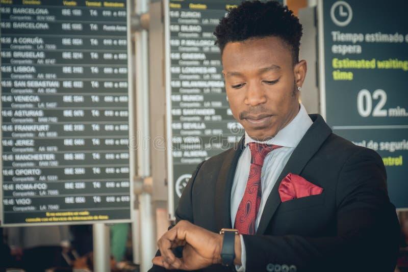 Hombre de negocios joven que mira su reloj elegante en el aeropuerto en f fotografía de archivo