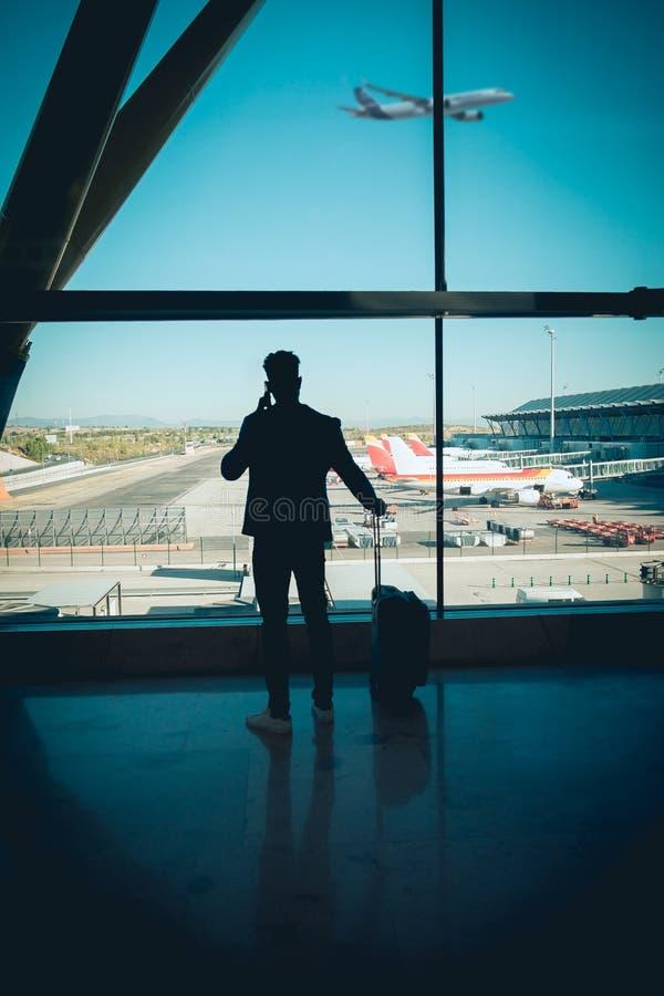 Hombre de negocios joven que mira a través de la ventana en la charla del aeropuerto foto de archivo libre de regalías