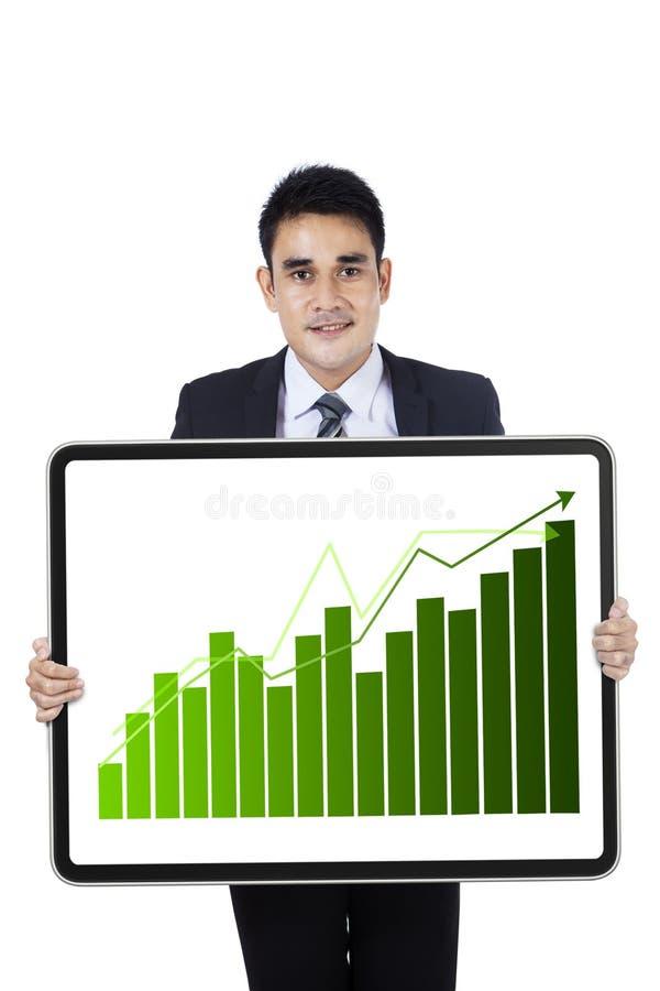 Hombre de negocios joven que muestra el gráfico del crecimiento imagen de archivo