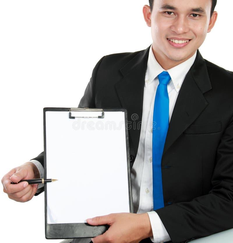 Hombre de negocios joven que muestra el sujetapapeles en blanco fotografía de archivo libre de regalías