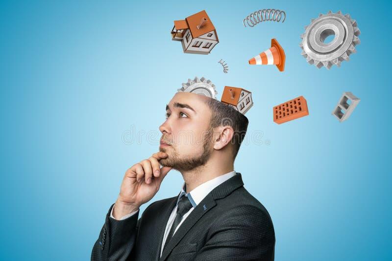 Hombre de negocios joven que piensa con las casas, las ruedas de engranaje, los ladrillos y el vuelo blancos del cono del tráfico foto de archivo