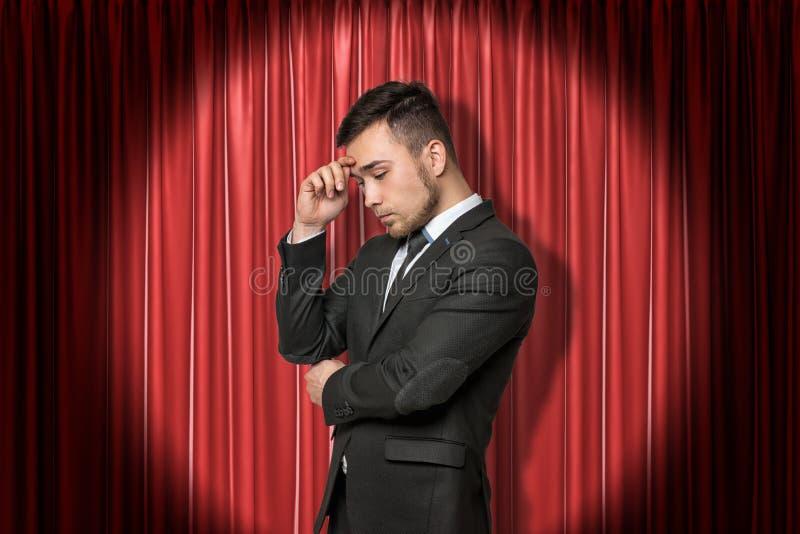 Hombre de negocios joven que piensa en fondo rojo de las cortinas de la etapa imagen de archivo