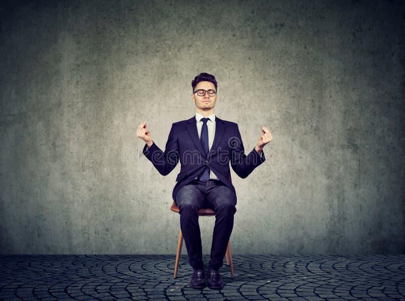 Hombre de negocios joven que reflexiona sobre la silla fotos de archivo