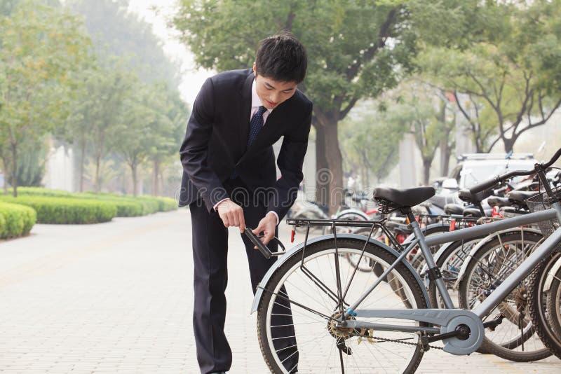 Hombre de negocios joven que se cierra encima de su bicicleta en una calle de la ciudad en Pekín fotografía de archivo libre de regalías