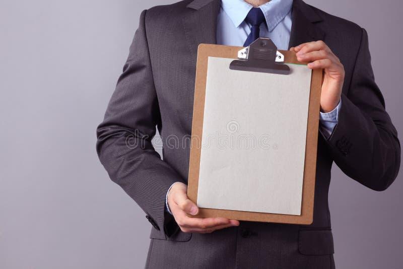 Hombre de negocios joven que se coloca con la carpeta, en fondo gris fotos de archivo libres de regalías