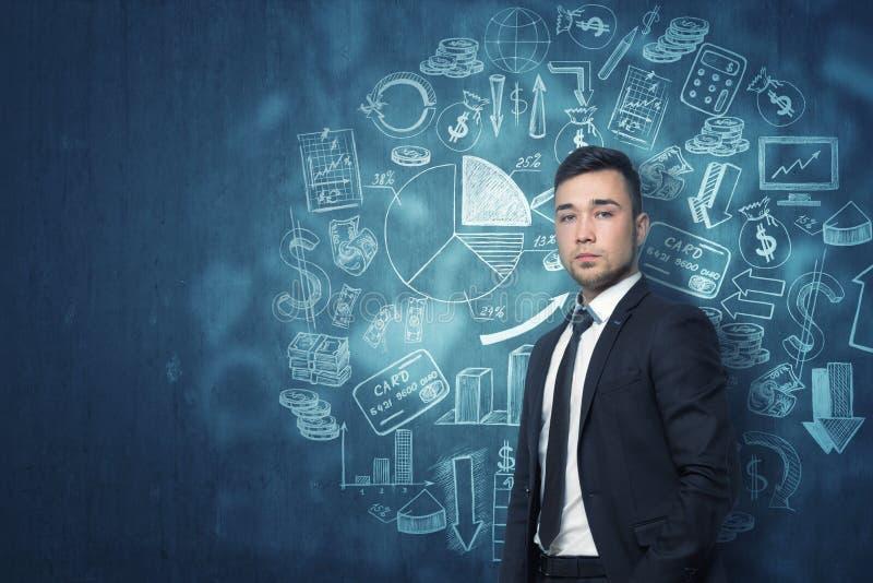 Hombre de negocios joven que se coloca delante de la pared azul marino con diversos bosquejos financieros foto de archivo libre de regalías