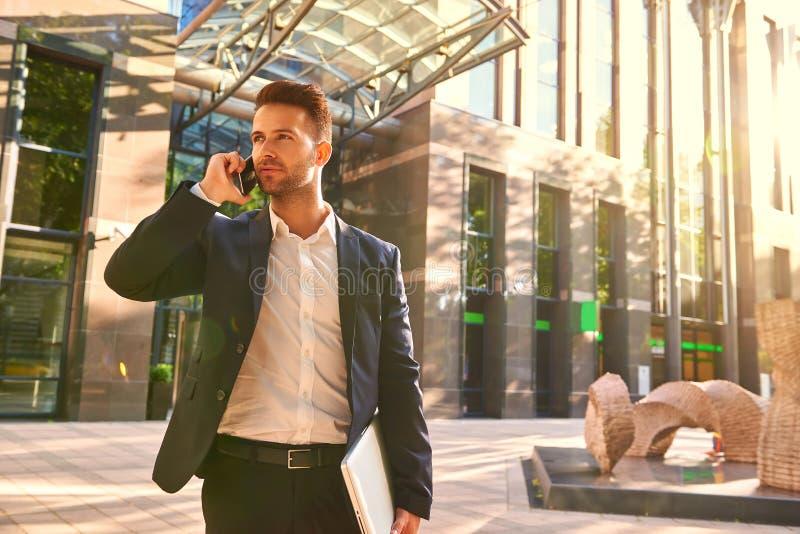 Hombre de negocios joven que se coloca delante del edificio de oficinas y del t imagen de archivo libre de regalías