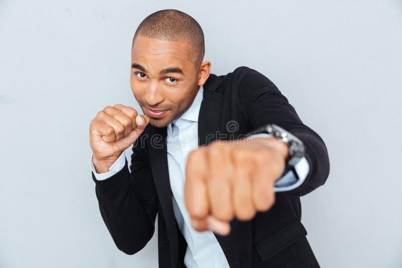 Hombre de negocios joven que se coloca en la posición del boxeador fotos de archivo