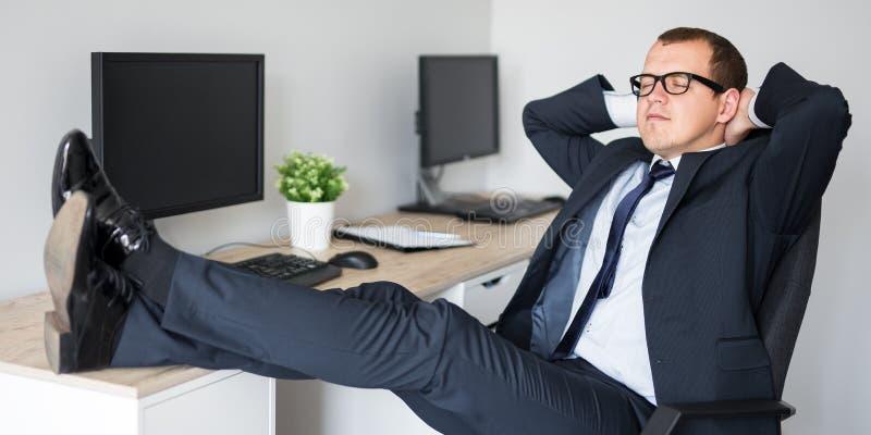 Hombre de negocios joven que se relaja con las piernas en la tabla imagen de archivo