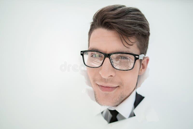 Hombre de negocios joven que se rompe a través de una pared de papel fotos de archivo
