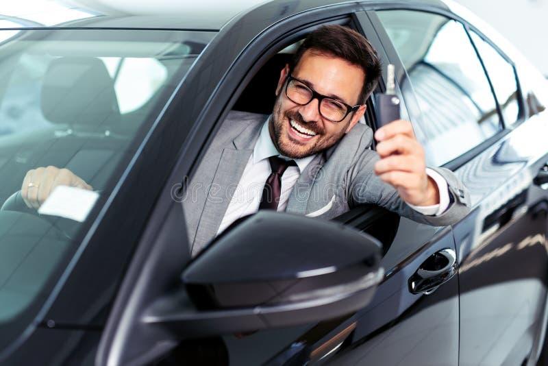Hombre de negocios joven que se sienta en coche y que muestra llaves del coche en la sala de exposición de la concesión de coch fotografía de archivo libre de regalías