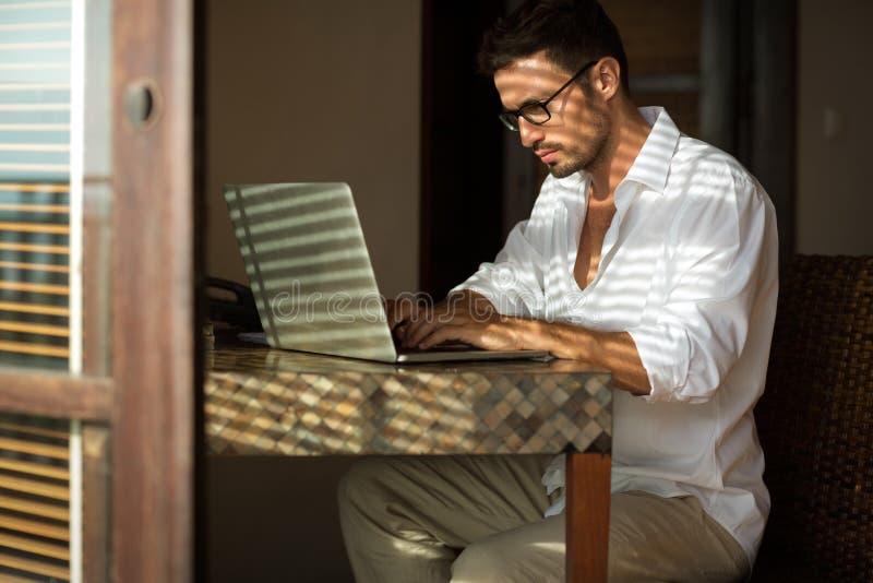 Hombre de negocios joven que se sienta en el escritorio, usando el ordenador portátil foto de archivo