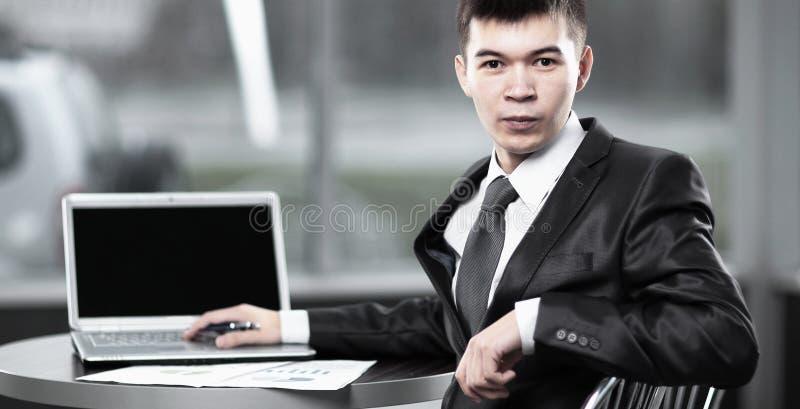 Hombre de negocios joven que se sienta en el lugar de trabajo y que mira la c?mara imagenes de archivo