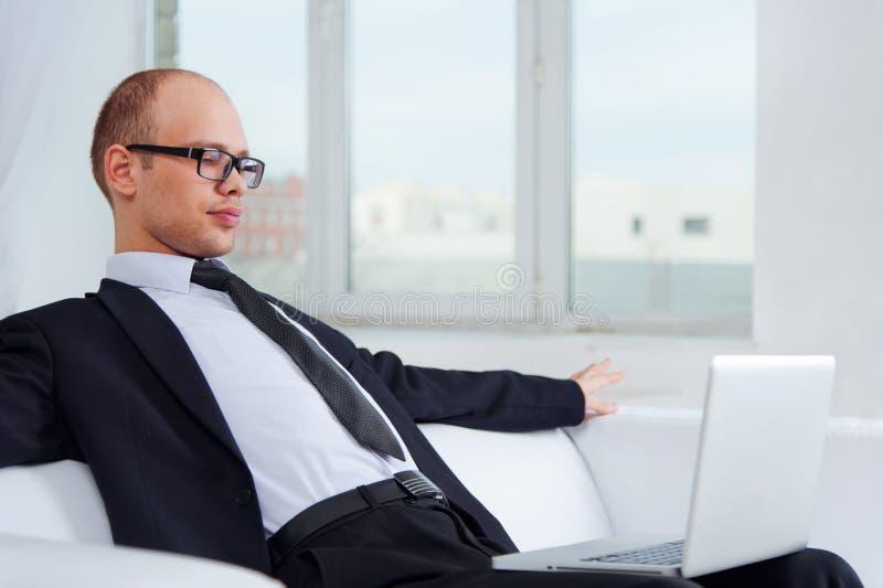 Hombre de negocios joven que se sienta en el sofá con el ordenador portátil imagenes de archivo