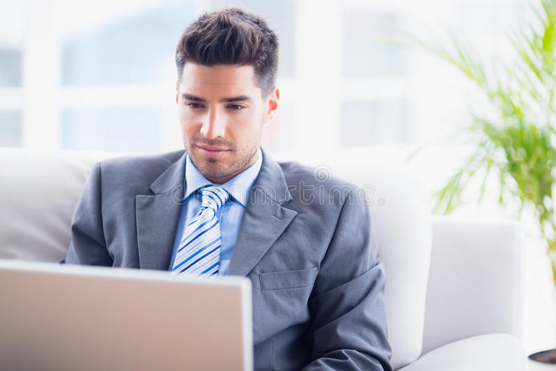 Hombre de negocios joven que se sienta en el sofá usando su ordenador portátil fotos de archivo libres de regalías