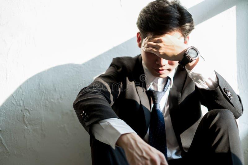 Hombre de negocios joven que se sienta en la oficina que siente cansada y subrayada, concepto del negocio imagenes de archivo