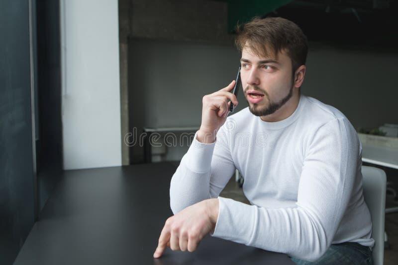 Hombre de negocios joven que se sienta en la oficina en la tabla y que soluciona problemas en un teléfono móvil fotos de archivo libres de regalías