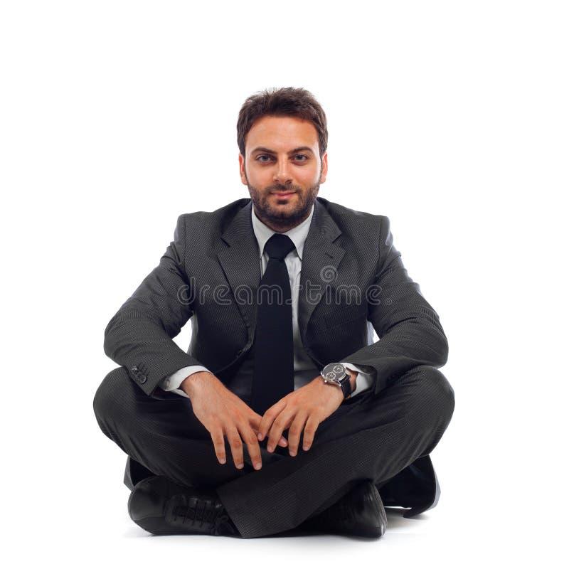 Hombre de negocios joven que se sienta en la tierra imagen de archivo libre de regalías