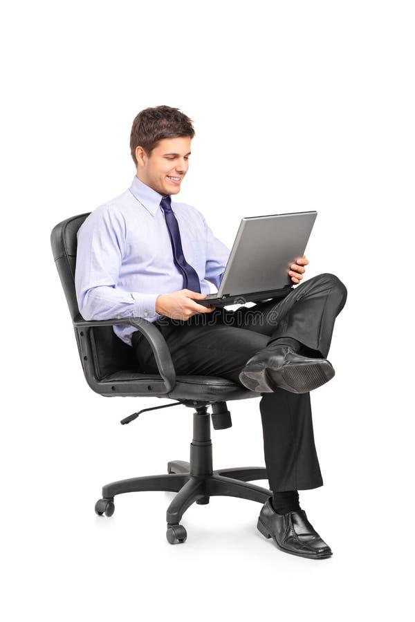 Hombre de negocios joven que se sienta en silla de la oficina fotos de archivo