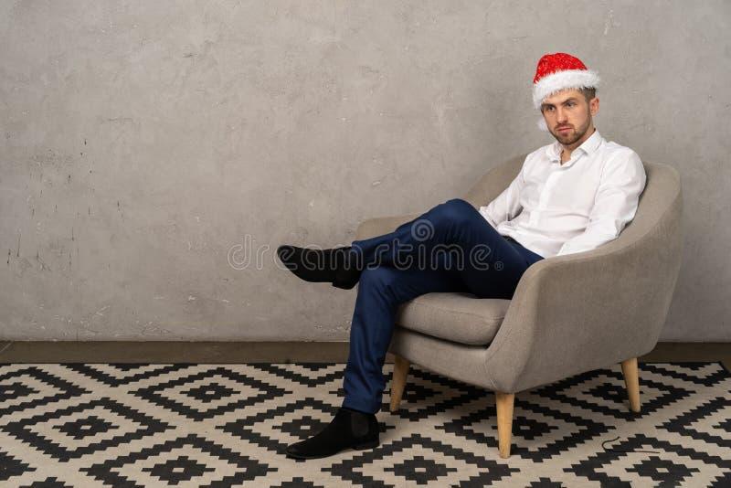 Hombre de negocios joven que se sienta en silla en el sombrero de santa mientras que agujerea el partido del Año Nuevo en la ofic fotos de archivo