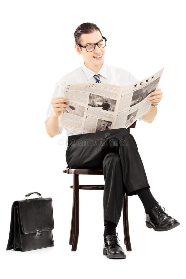 Hombre de negocios joven que se sienta en un banco y que lee un periódico imágenes de archivo libres de regalías