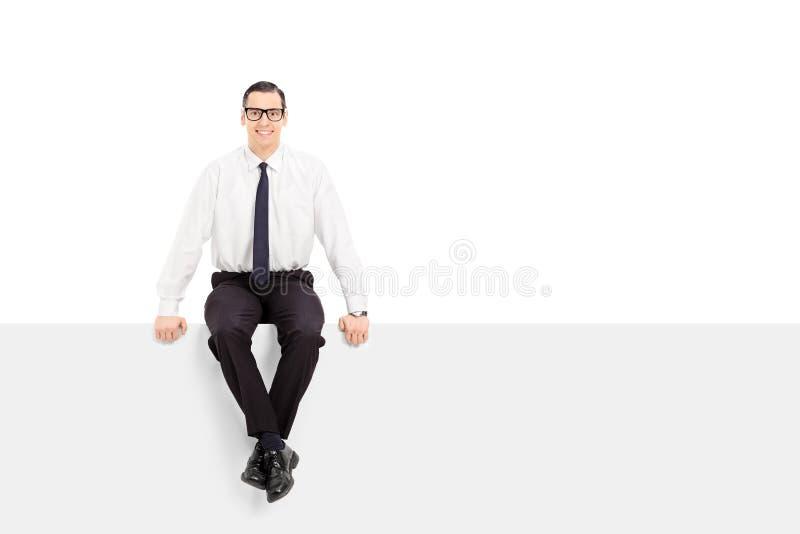 Hombre de negocios joven que se sienta en una cartelera en blanco fotografía de archivo libre de regalías