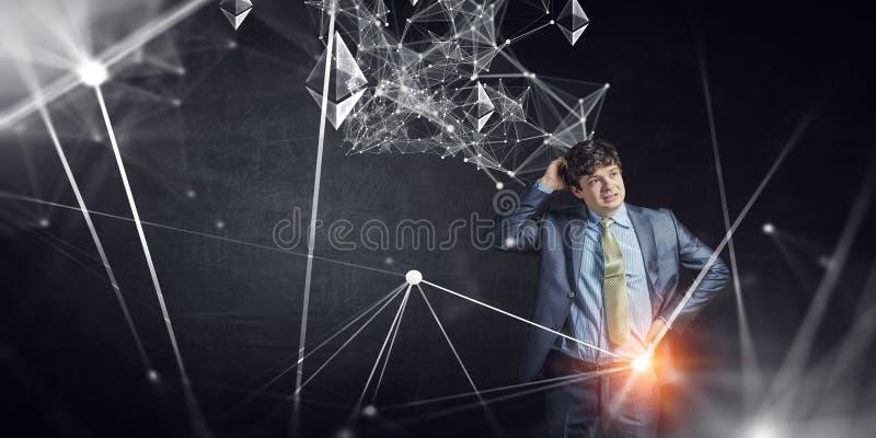 Hombre de negocios joven que soluciona un problema T?cnicas mixtas foto de archivo