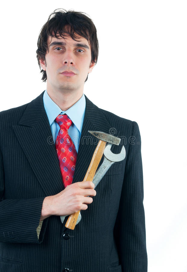 Hombre de negocios joven que sostiene el martillo y la llave como metaphore el suyo imagen de archivo