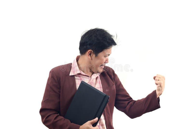 Hombre de negocios joven que sostiene el ordenador portátil y que celebra en alegre y fotos de archivo