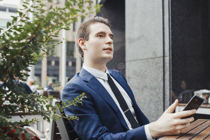 Hombre de negocios joven que sostiene el teléfono móvil a disposición y que mira a un lado imagen de archivo