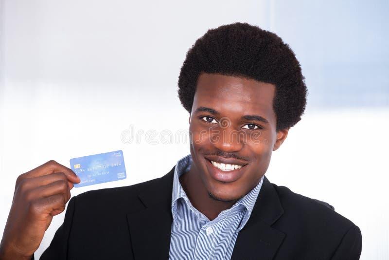 Hombre de negocios joven que sostiene la tarjeta de crédito foto de archivo