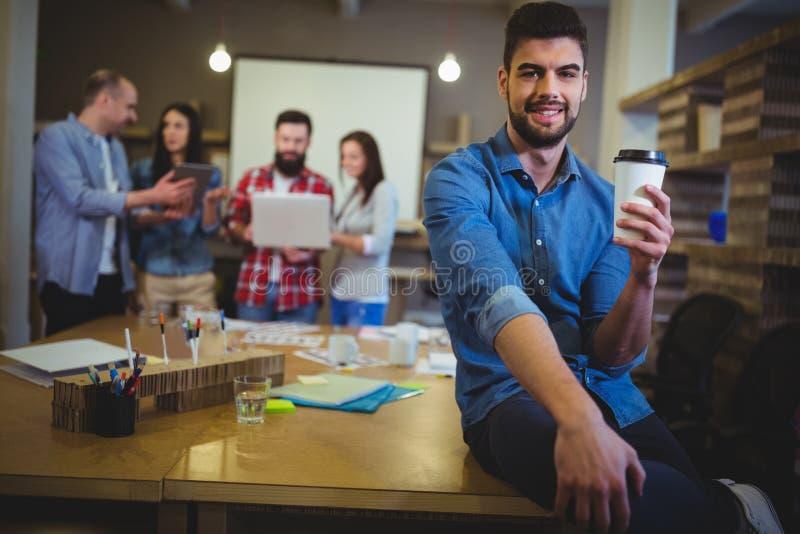 Hombre de negocios joven que sostiene la taza disponible mientras que se sienta en la tabla imagen de archivo libre de regalías