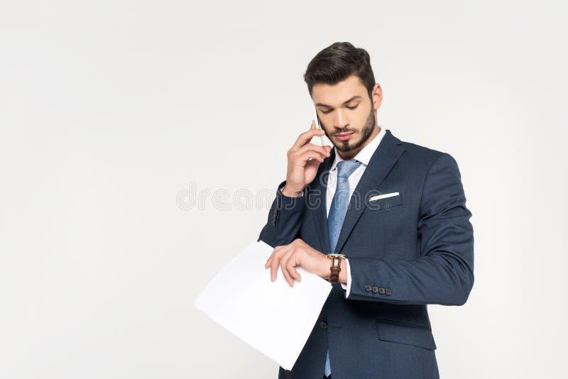 hombre de negocios joven que sostiene los papeles y que habla en smartphone mientras que comprueba el reloj imágenes de archivo libres de regalías