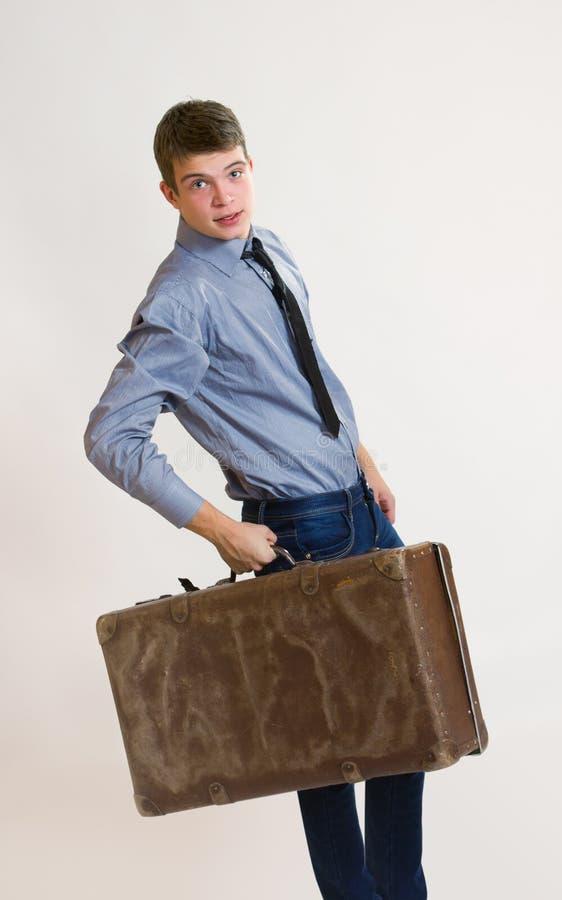 Hombre de negocios joven que sostiene su maleta vieja fotos de archivo