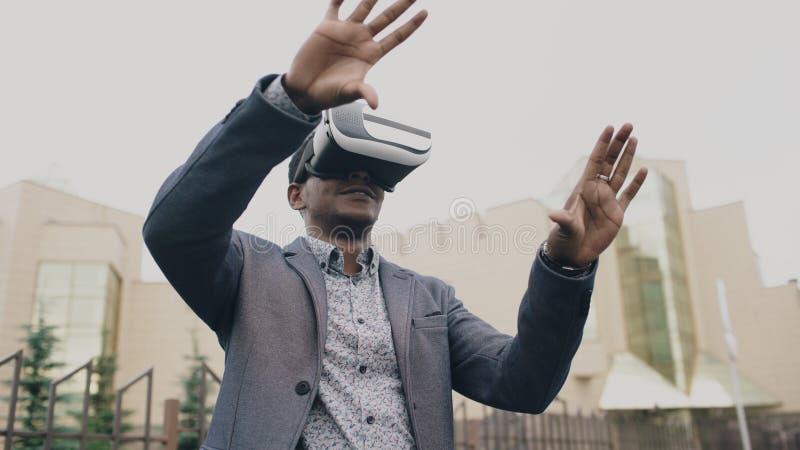 Hombre de negocios joven que tiene experiencia de VR usando las auriculares de la realidad virtual 360 al aire libre imagen de archivo libre de regalías