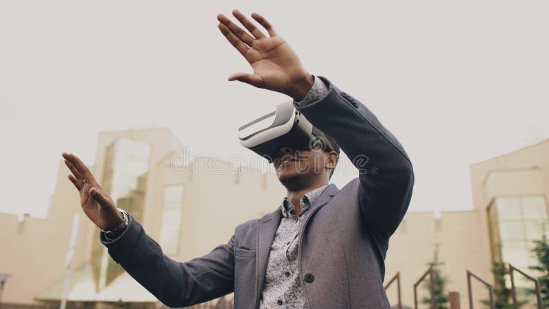 Hombre de negocios joven que tiene experiencia de VR usando las auriculares de la realidad virtual 360 al aire libre fotografía de archivo