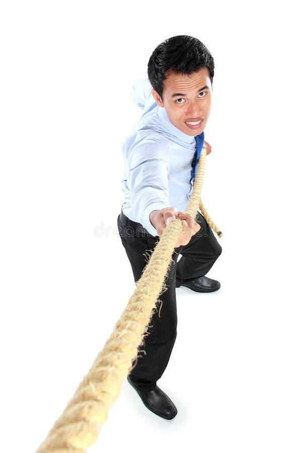 Hombre de negocios joven que tira de una cuerda mientras que se coloca imagen de archivo libre de regalías