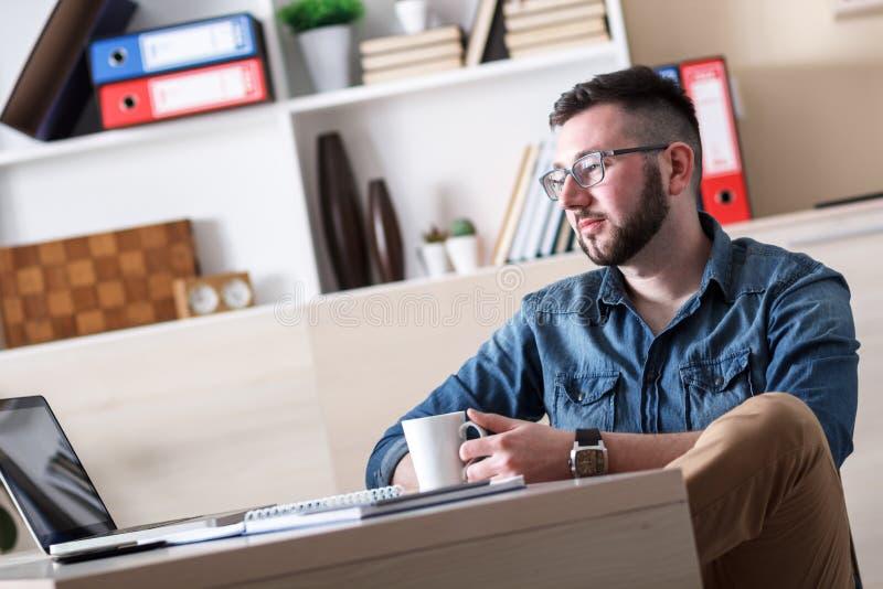 Hombre de negocios joven que toma el descanso para tomar café en su oficina imagen de archivo
