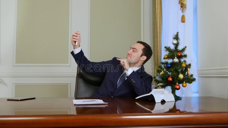 Hombre de negocios joven que toma la foto del selfie con el árbol del Año Nuevo usando el teléfono móvil en oficina imagenes de archivo