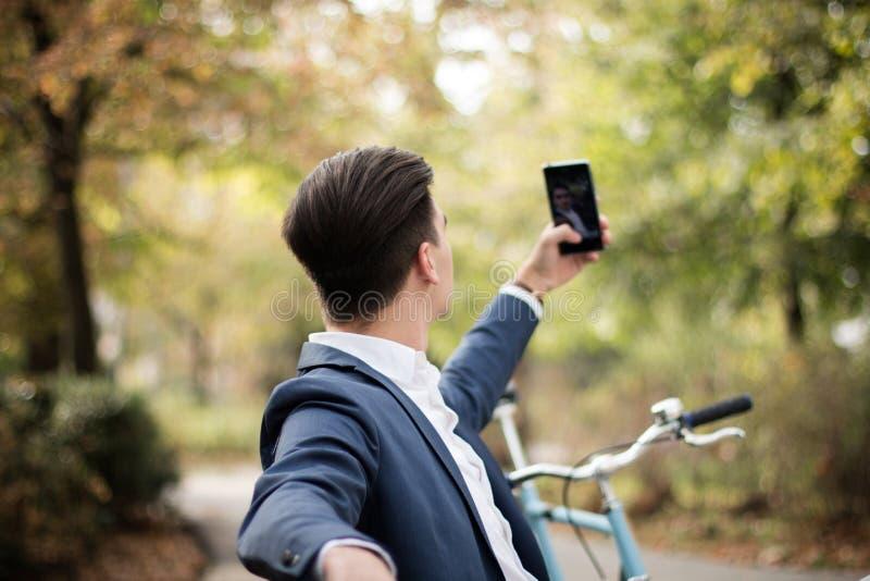 Hombre de negocios joven que toma un selfie con su smartphone al aire libre en un parque fotografía de archivo libre de regalías