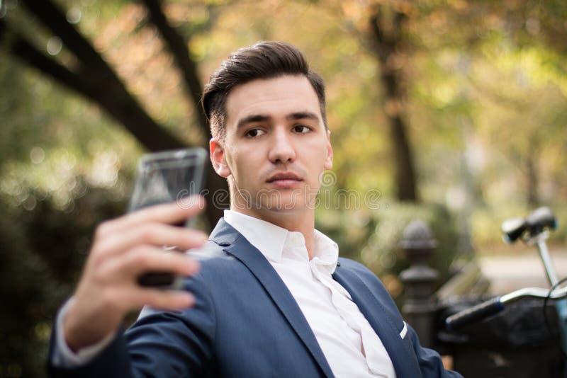 Hombre de negocios joven que toma un selfie con su smartphone al aire libre en un parque imagenes de archivo