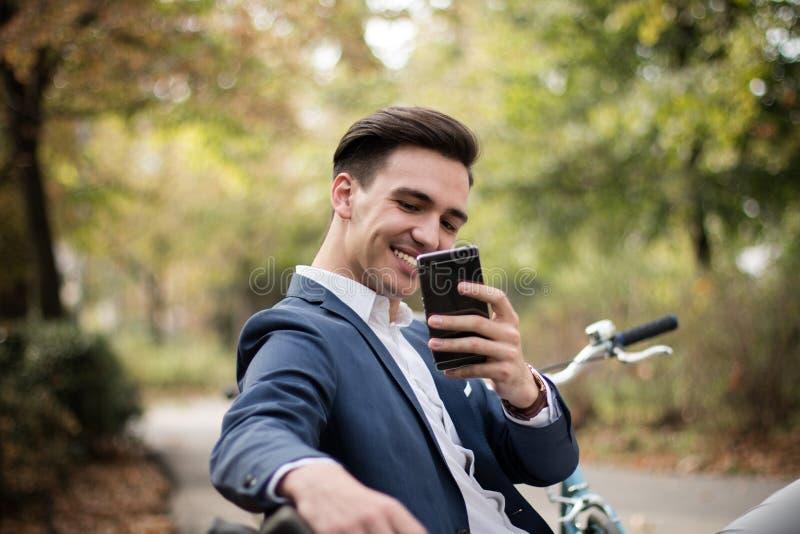Hombre de negocios joven que toma una foto con su smartphone al aire libre en un parque fotografía de archivo libre de regalías