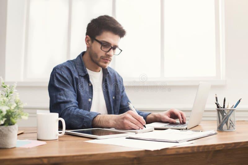 Hombre de negocios joven que trabaja con el ordenador portátil en oficina fotos de archivo