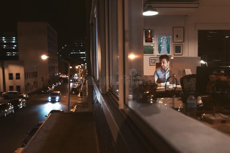 Hombre de negocios joven que trabaja dentro de una oficina en la noche foto de archivo libre de regalías