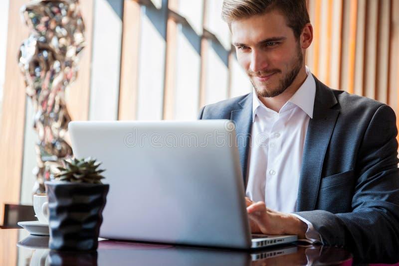 Hombre de negocios joven que trabaja en el ordenador portátil, sentándose en el pasillo del hotel que espera alguien imagen de archivo libre de regalías