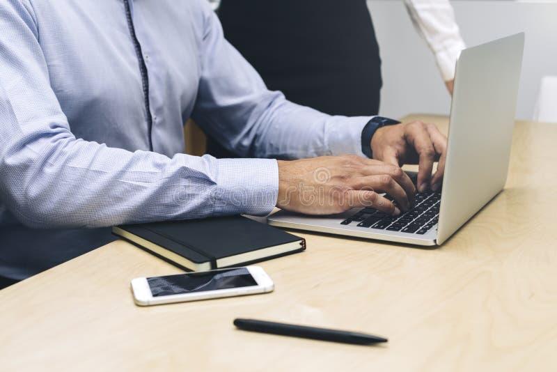 Hombre de negocios joven que trabaja en el ordenador port?til en oficina moderna foto de archivo libre de regalías