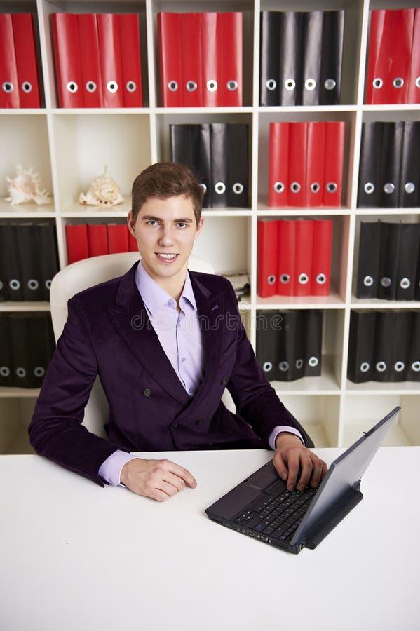 Hombre de negocios joven que trabaja en la computadora portátil imagen de archivo libre de regalías