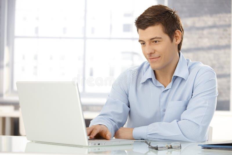 Hombre de negocios joven que trabaja en oficina imagen de archivo libre de regalías
